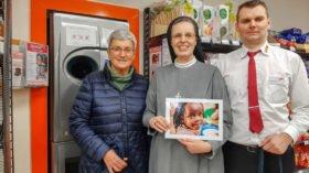 Schwester Maria Thoma Dikow dankt tegut-Marktleiter Sebastian Jaster (r.) für das Aufhängen der Pfandboxen und Annelore Kleppe für die regelmäßige Leerung. Foto: SMMP/Sr. Theresia Lehmeier
