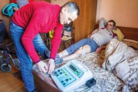 Hausbesuch in Rumänien: Der 55-jährige Dorin hatte einen Schlaganfall. Krankenschwester Viorica und Physiotherapeut Ionut helfen ihm im wahrsten Sinne des Wortes wieder auf die Beine. Foto: SMMP/Ulrich Bock